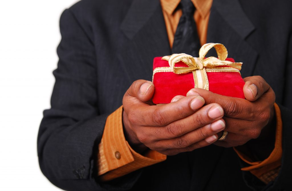African-American male hands holding a red velvet box with gold ribbon.